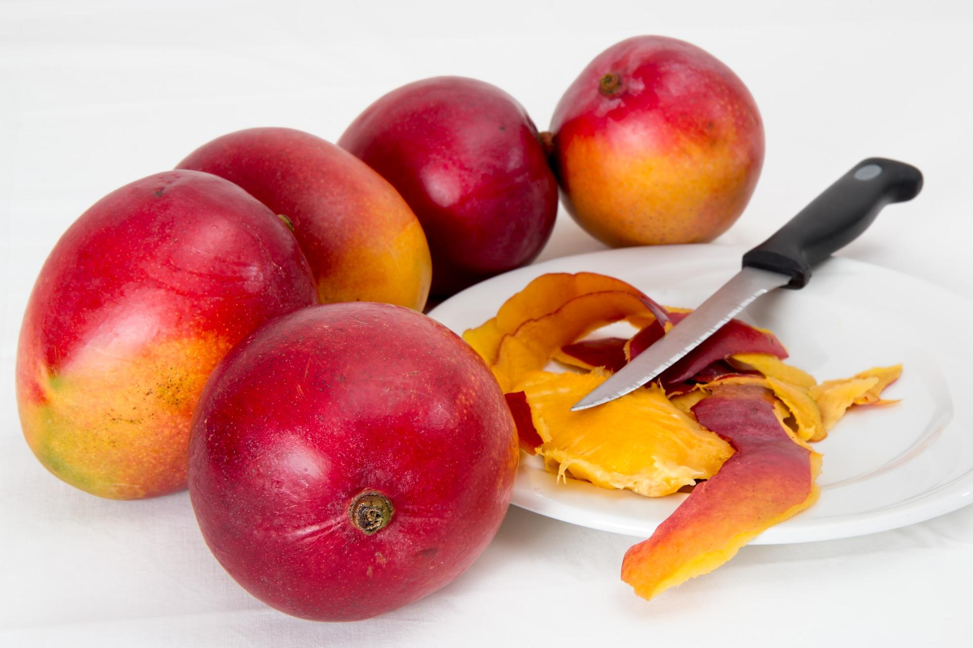 5 mango fruits around white plate with knife and mango peels