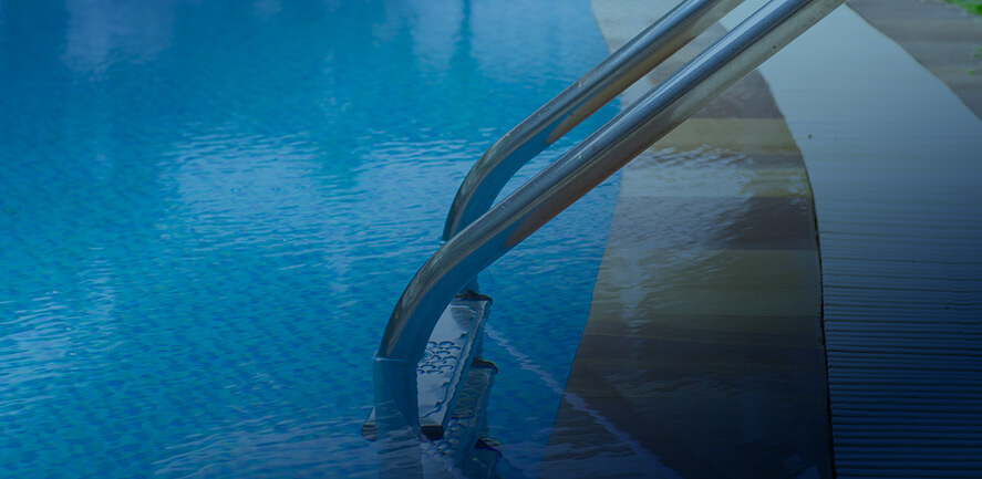 edge of a swimming pool with ladder descending into the water